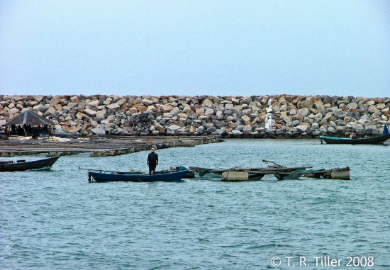 A fisherman in front of his house by the breakwater.