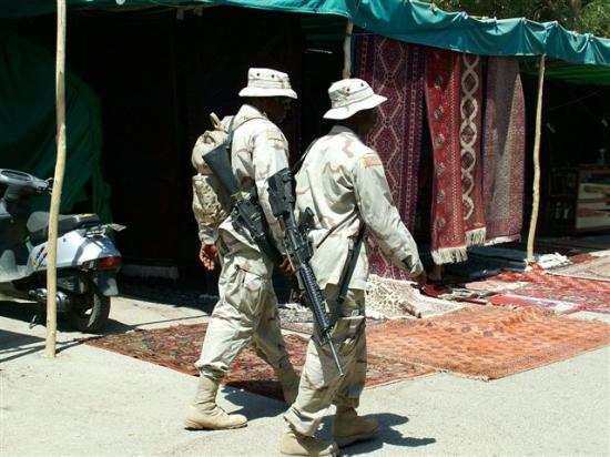 Two soldiers stroll through a Bazaar in downtown Baghdad's International (Green) Zone. The Bazaar...