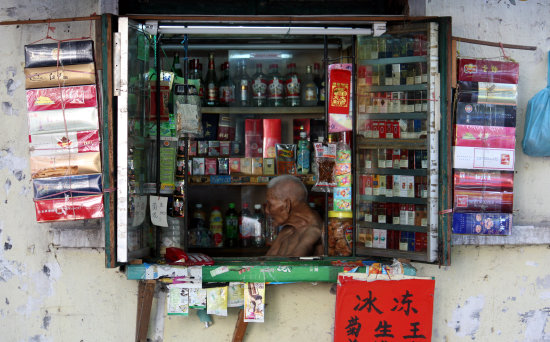 Cigarette and Rice Wine 'shop' ( a window in his house really) . Nanning, China, 24th July 2011