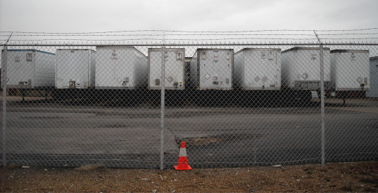 semi tractor trailers chainlink fence orange cone parkinglot