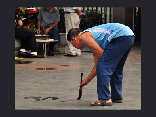 painting calligraphy with water on the pavement in the park doesn't last but gives him pleasure ...