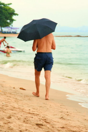 man with umbrella on the beach colour postcard