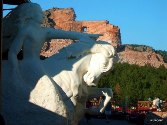 The finished sculpture of crazy horse in front the on going work