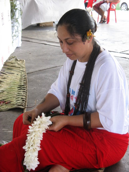 Une femme tresse un collier de fleurs