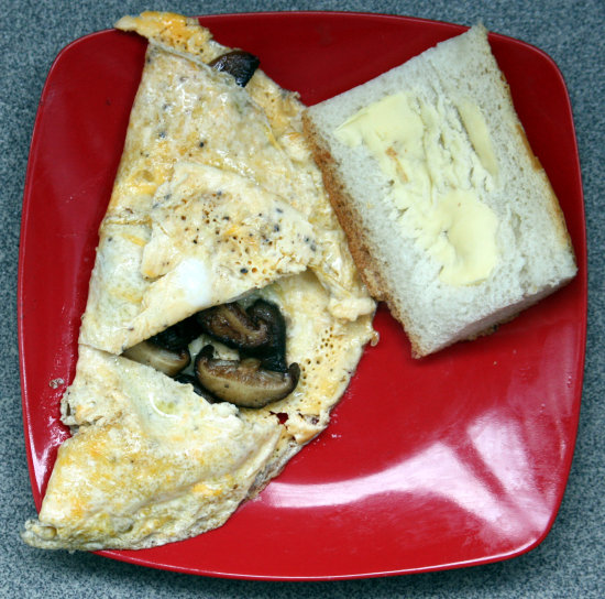 Two duck egg / three mushroom (button mushrooms, shiitake and cèpes) omelette. Bread and butter.