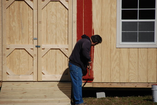 building work painting staining barn red