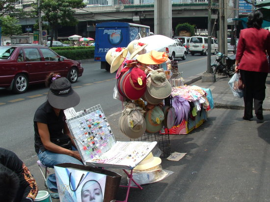 Street merchant sells their wares on the packed sidewalks of Bangkok Thailand