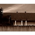 house wall roof fence tree sky clouds sepia monochome