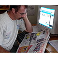 man paper newspaper computor wait reading