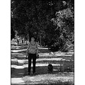 street candid walking woman dog tree bush road grass bw