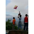 Kids flying a kite on the edge of a cliff.