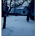 street houses fence trees bush snow old woman monochrome